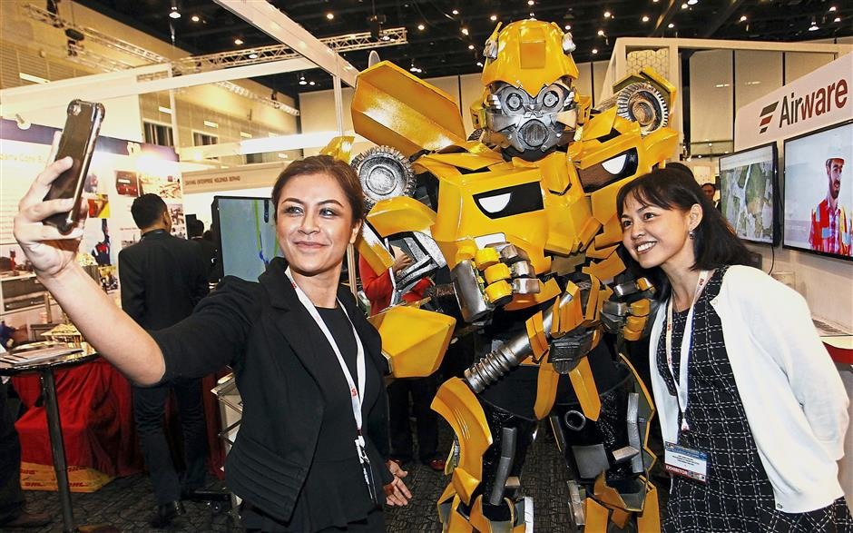 Visitors Norhashimah Tukimin (left) and Amy Chew taking a wefie with a Bumble Bee, a Transformers robot, at the exhibition booth during the 4th International Energy Week 2018 at the Borneo Convention Centre Kuching on Tuesday. - ZULAZHAR SHEBLEE / THE STAR