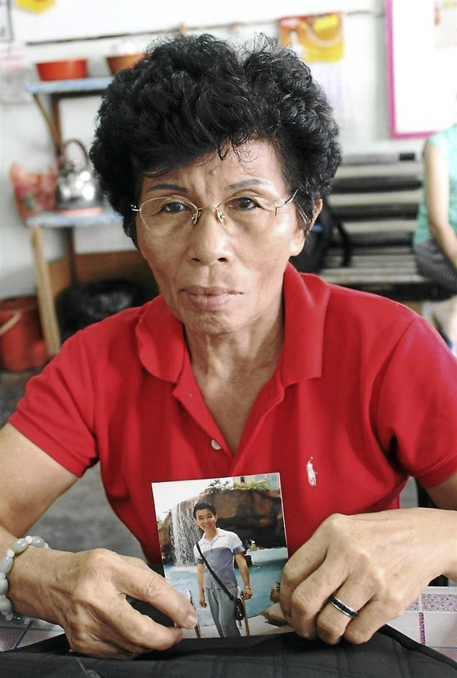 Missing her son: Chee Yoke Foong holding a picture of his son Tan Hoi Chee, who has been missing for about four years.