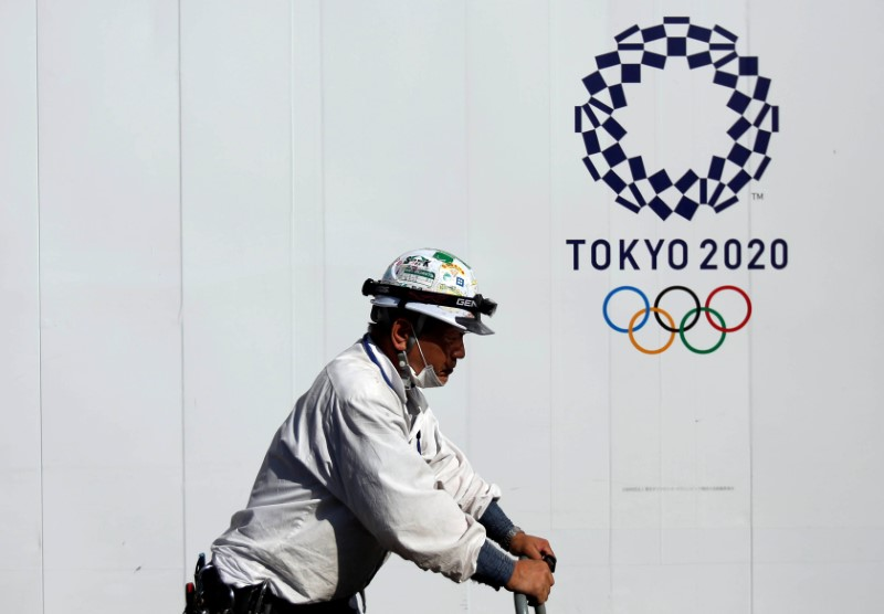 FILE PHOTO: A construction worker walks past at a construction site of a building displaying Tokyo 2020 Olympics emblem in Tokyo, Japan May 23, 2017. REUTERS/Issei Kato
