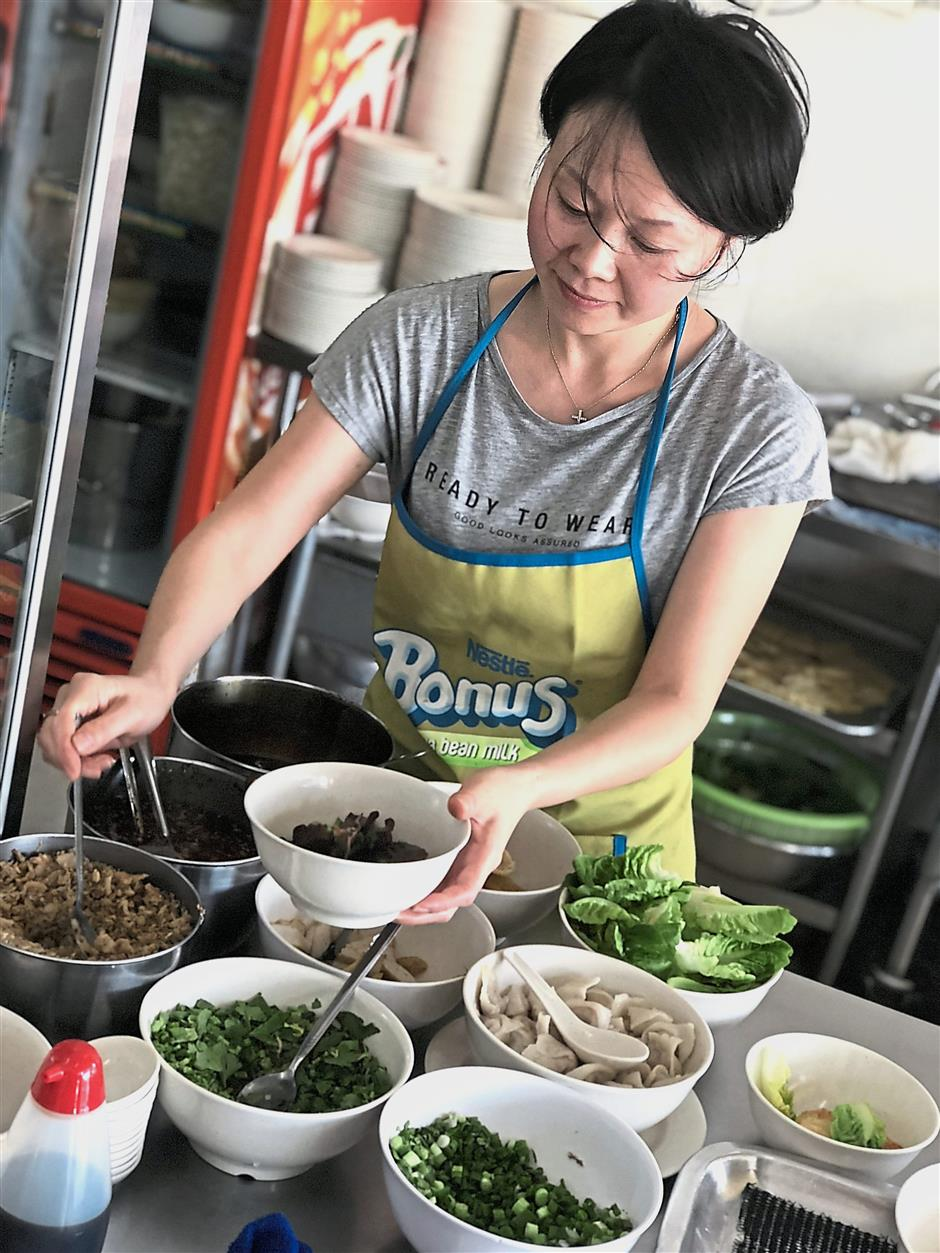Lims wife Tan Chun Chun, 39, will help him to cook the noodles when he is busy making fish balls and fish cake inside the kitchen.