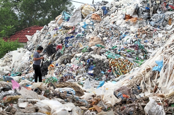 Piling up: A man observing mounds of plastic waste at the waste storage centre at IGB Industrial Area.