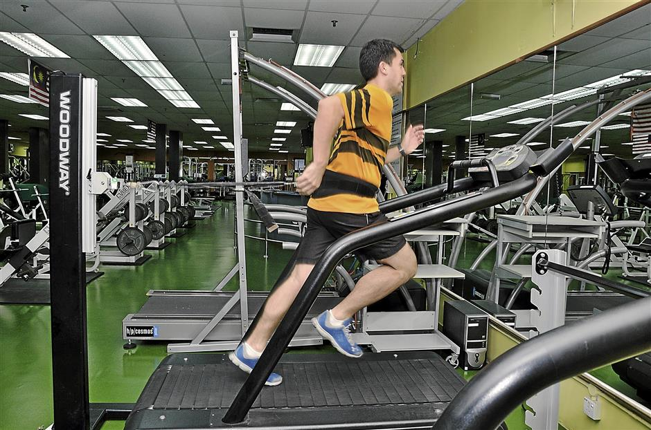 Sean Sturgess demonstrates how athletes train at the NIS gym.