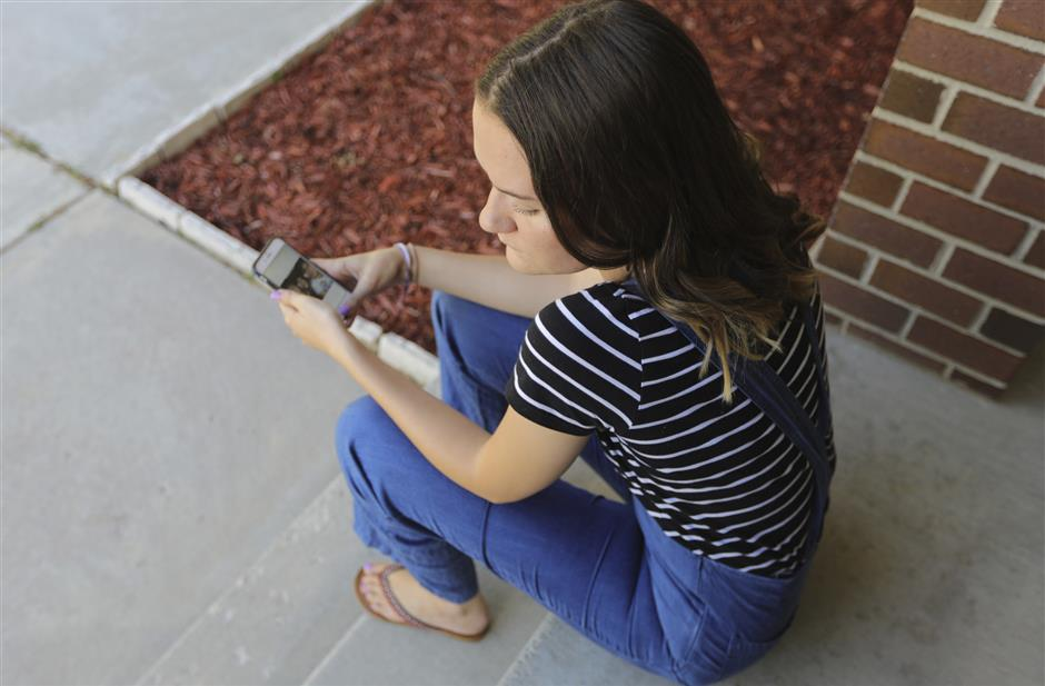 In this Monday, July 22, 2019, photo, Rachel Whalen looks at her phone at her home in Draper, Utah. Whalen remembers feeling gutted in high school when a former friend would mock her online postings, threaten to unfollow or unfriend her on social media and post inside jokes about her to others online. The cyberbullying was so distressing that Whalen even contemplated suicide. There's a rise in cyberbullying nationwide, with three times as many girls reporting being harassed online or by text message than boys, according to the National Center for Education Statistics. (AP Photo/Rick Bowmer)
