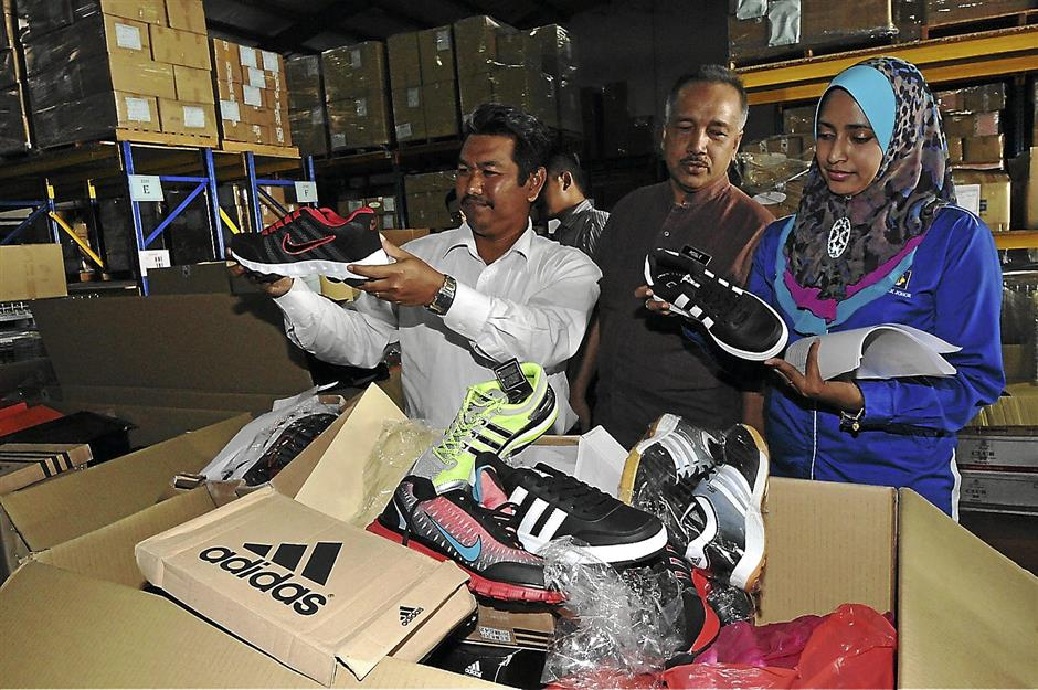 Johor Domestic Trade, Cooperatives and Consumerism Ministry (KPDNKK) director Ayub Abd Rahman (left) with other department officers looking at fake goods at KPDNKK store here in Johor Baru on June 14. Pic by ABDUL RAHMAN EMBONG/The Star.