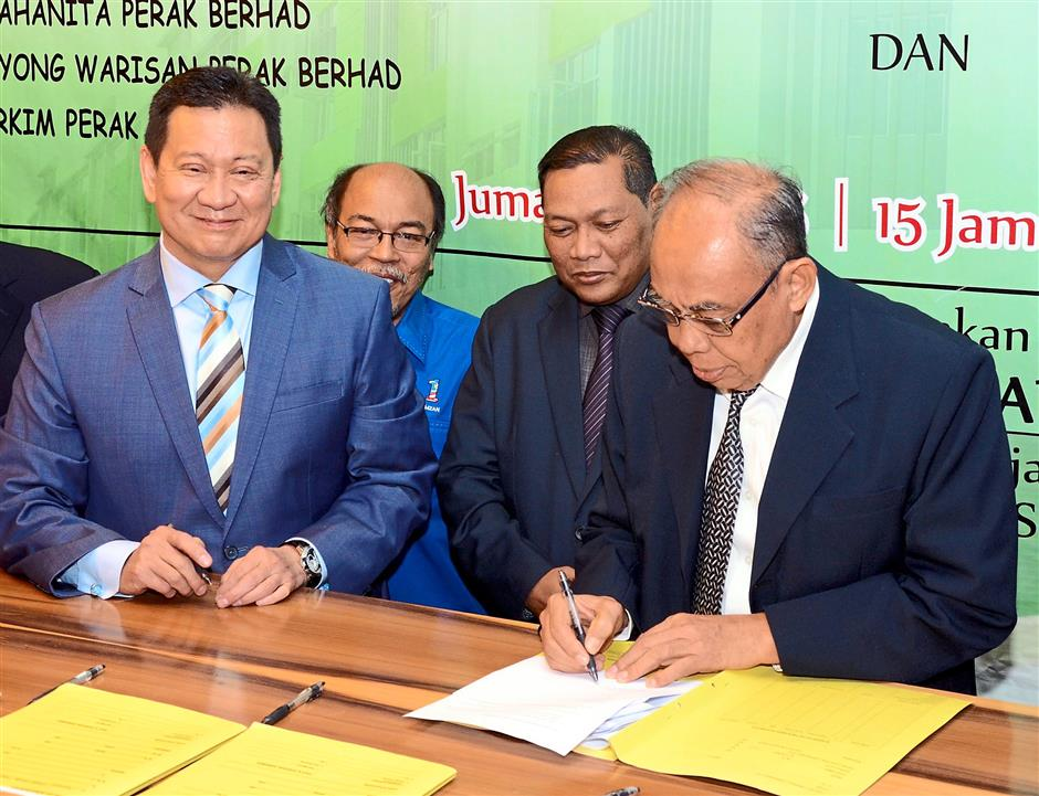Putting pen to paper: Lee (left) and Mohd Nizar (second from right) witnessing a representative (right) from Koperasi Keluarga Anjang Budiman Taiping Bhd signing the contract.
