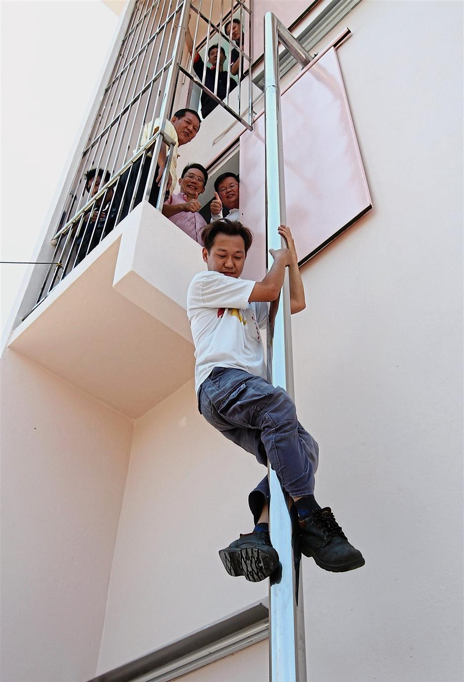 (From left) Hock Keong, Alex and Chow Kon Yeow watching a firemen demonstrate how to slide down the pole at the newly completed fire station at Weld Quay. — Photos: CHIN CHENG YEANG/The Star