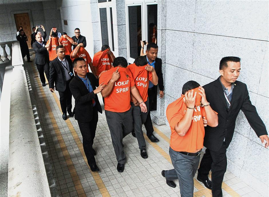 Taken away: MACC officers escorting the seven PMD officers at the magistrate's court in Putrajaya. Inset: Hasanah