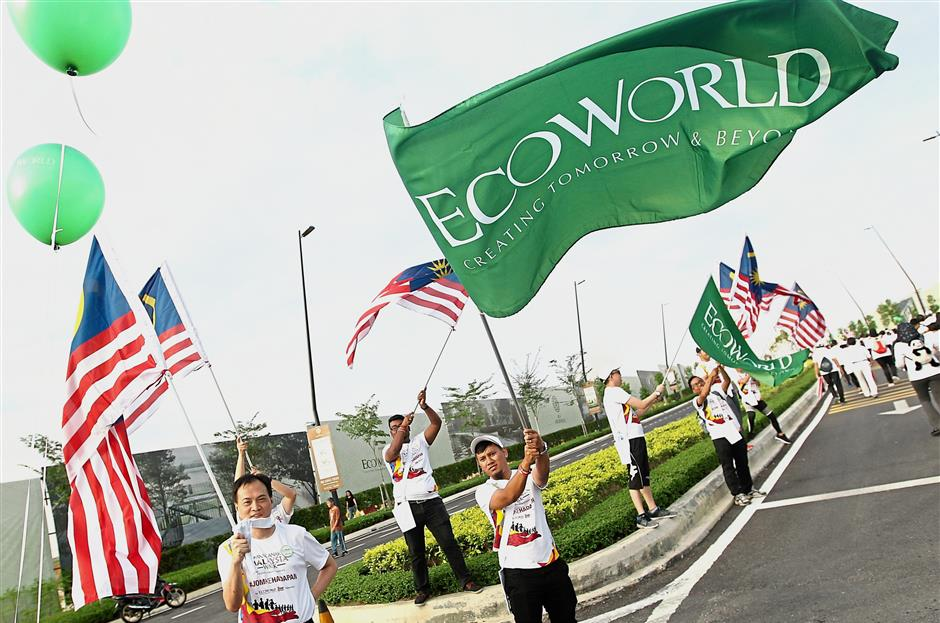 Volunteers waving flags to spur on participants during the AnakAnakMalaysia Walk at Eco Ardence.
