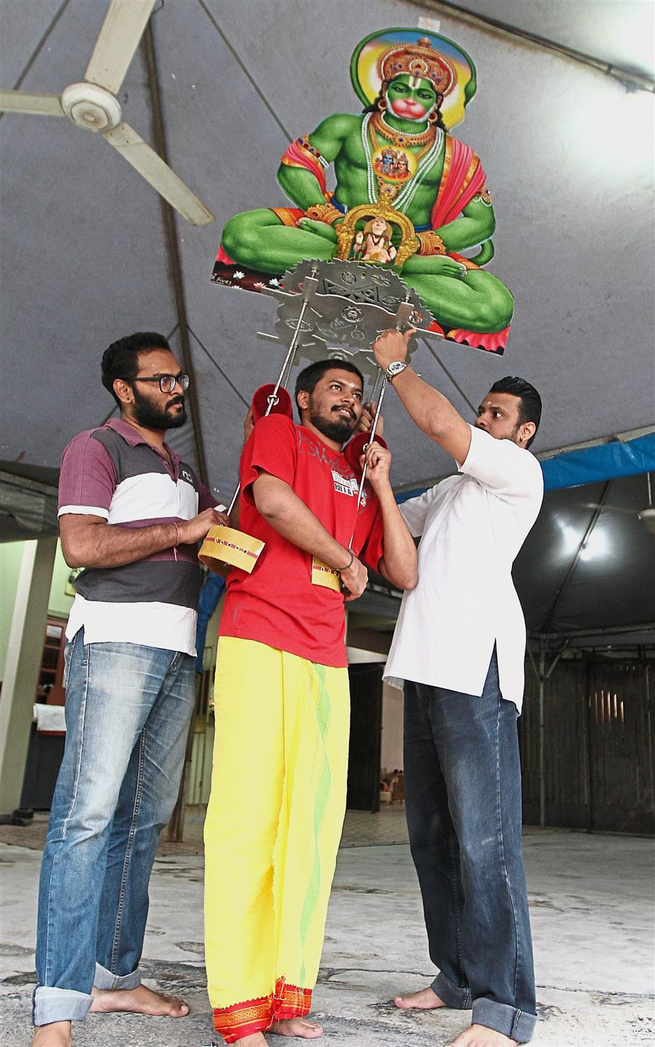 Sudhankumar (centre) being assisted by Uthaya Suthern (left) and Thinesh as he tests out a kavadi they built for Thaipusam.