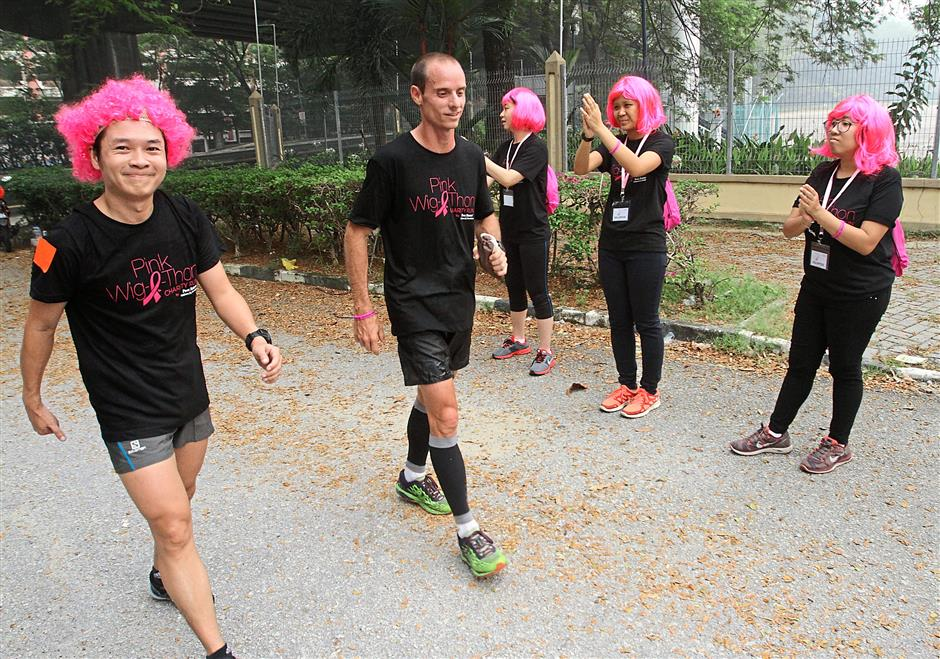 Runner up Lee Kee Hin (left) and winner of 10km Edwin Micas greeted at finishing line of PinkWigAthon run at Bukit Jalil. RAYMOND OOI/ The Star