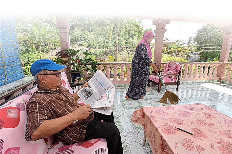 Mohd Hussin Yahya (left) sits leisurely outside the porch area of his single-storey brick home, with all the modern creature comforts he is now enjoying thanks to the monthly income he receives as owner of a 4.1ha oil palm land.