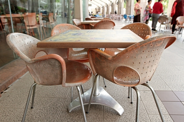 Worn-out tables and chairs at the outdoor seating of Selera Putra food court.