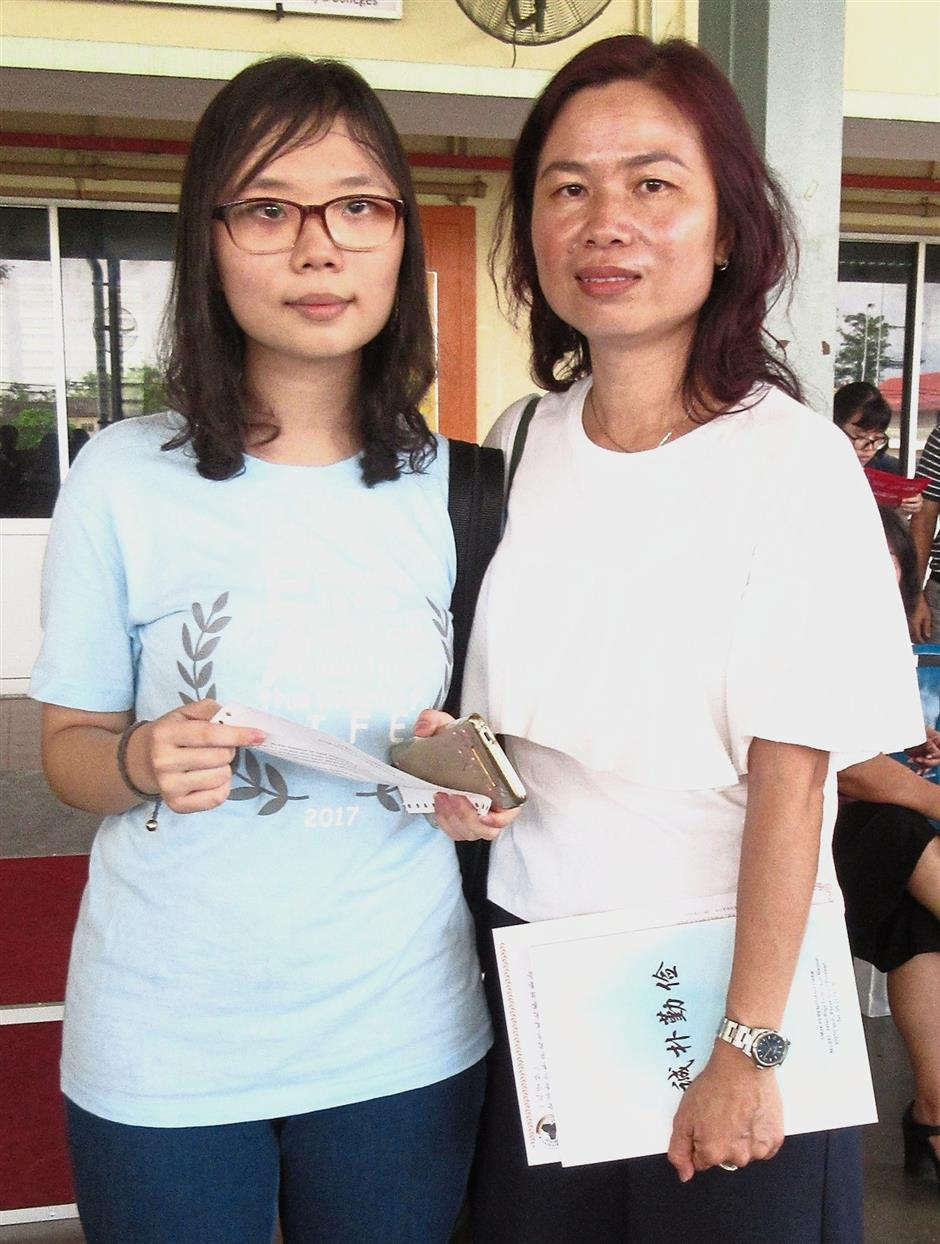 Weng Sam (left) took her vision impairment in her stride in scoring 4As and 2Bs in her SPM. With her is her mother Ho.