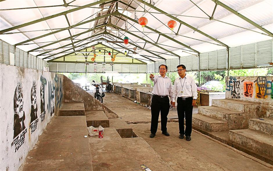 Thinking big: Wei Aik (left) and Penang municipal councillor Tan Kim Hooi checking out the vacant market.