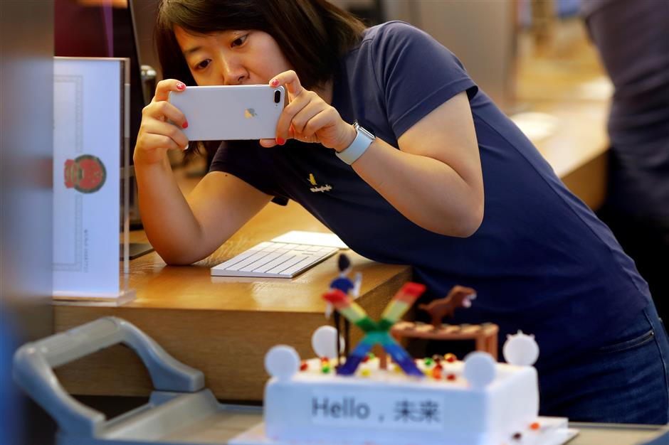 A member of Apple staff takes pictures as new iPhone X begins to sell at an Apple Store in Beijing, China November 3, 2017. REUTERS/Damir Sagolj