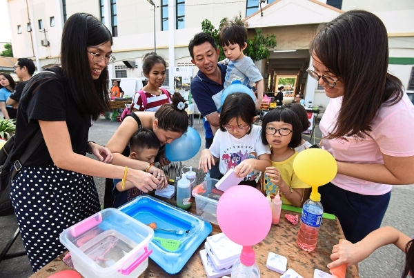 Joanne Ang (left) attending to customers at her water baby booth.