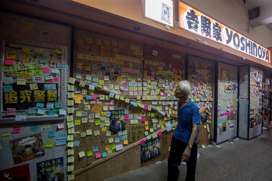 A pedestrian walks past protest notes covering a shuttered Yoshinoya restaurant in the Shatin district of Hong Kong, China, on Sunday, July 14, 2019. Hong Kong demonstrators gathered for another weekend of protests with a growing list of grievances, maintaining pressure on Chief Executiveu00a0Carrie Lamu00a0who was reported to have offered her resignation several times in recent weeks to her political masters in Beijing. Photographer: Paul Yeung/Bloomberg