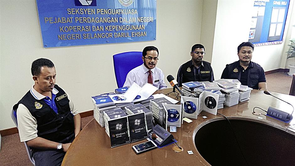Othman (in white) speaking at a meeting to announce the seizure of the counterfeit software.
