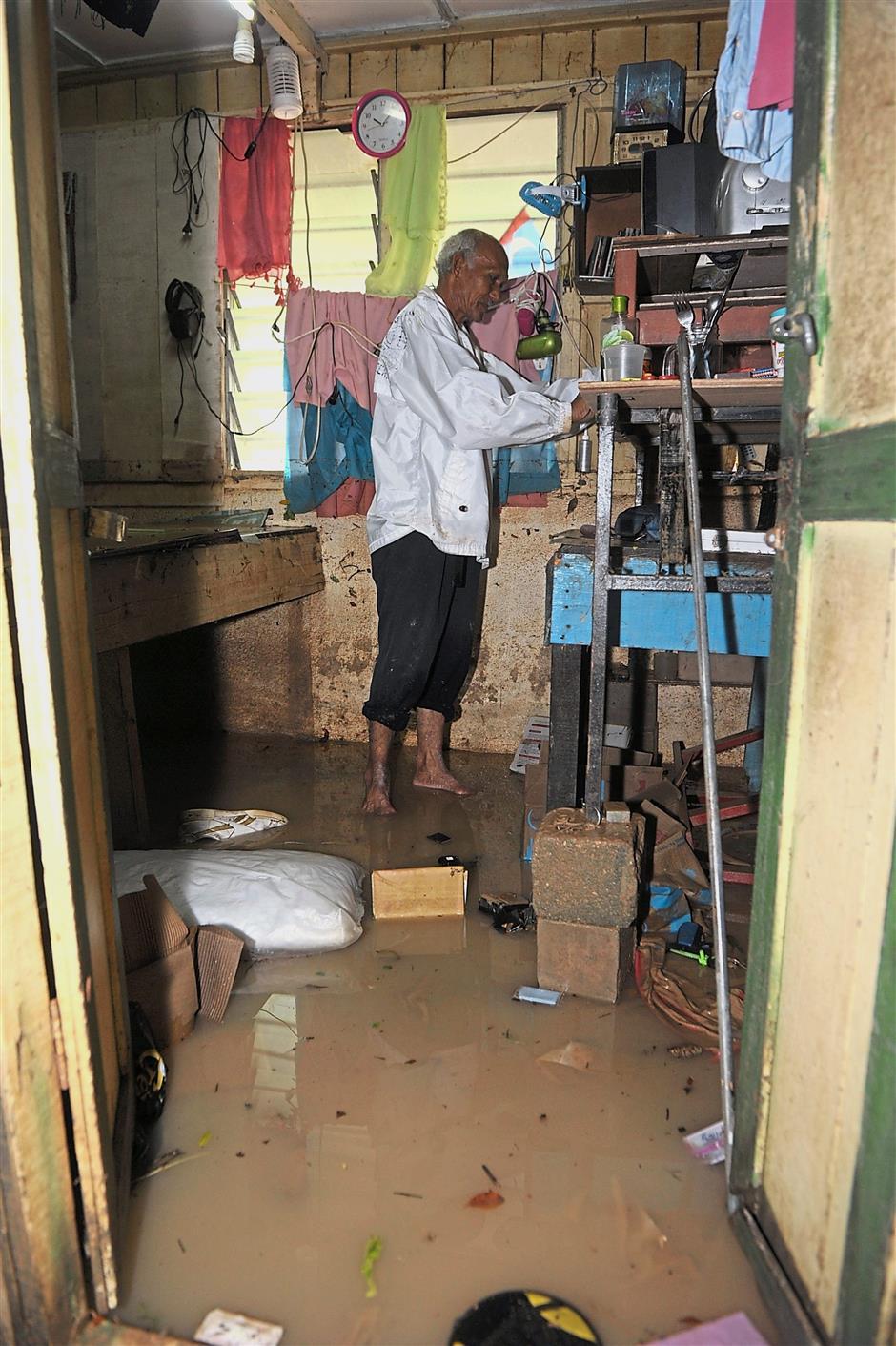 Samat Wan Chik, 73, inspecting some of the furniture in his house at Jalan Rawang off Jalan P. Ramlee after the flash flood.