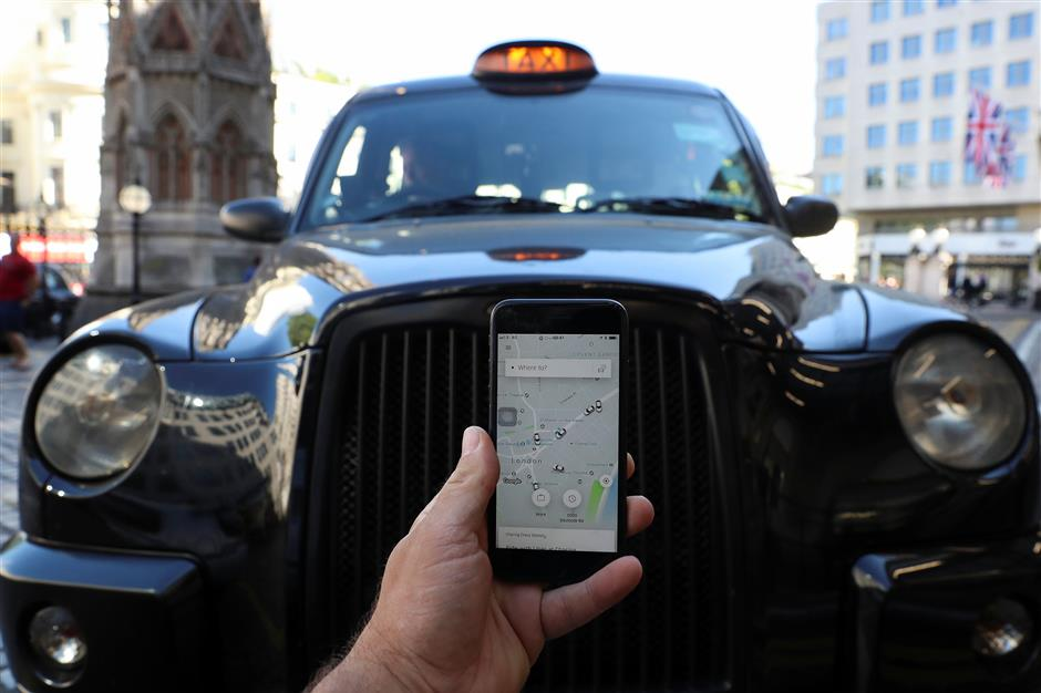 A photo illustration shows the Uber app and a black cab in London, Britain June 26, 2018. REUTERS/Simon Dawson/Illustration