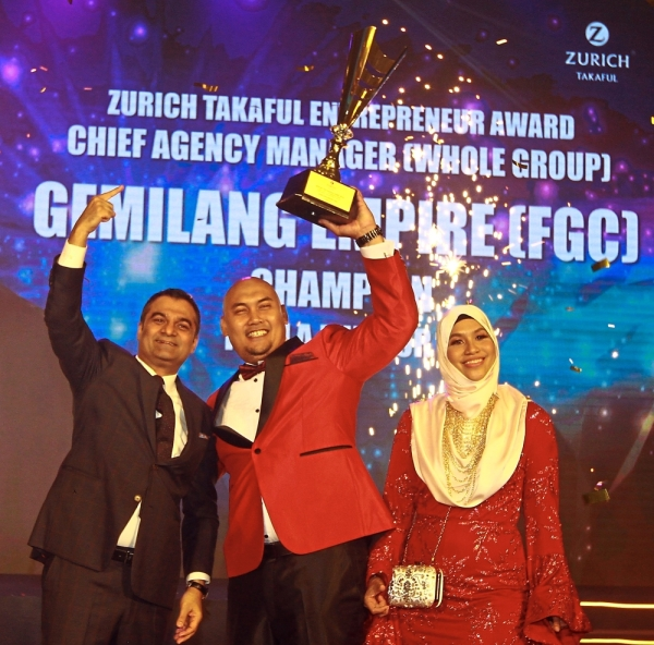 Mukesh (left) with Mohd Fahmi and his wife receiving one of the top two prestigious awards of the night. — Photos: CHAN TAK KONG/The Star