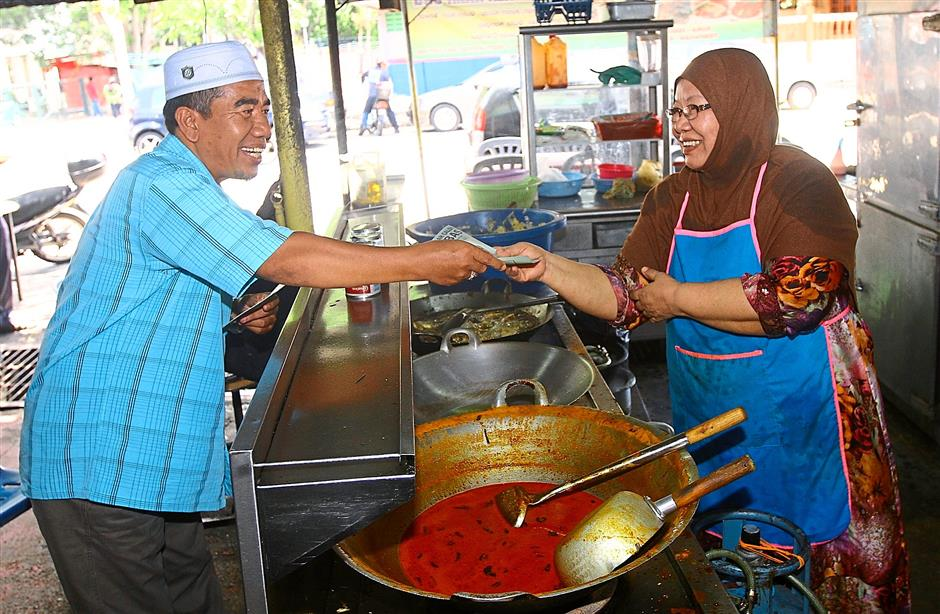 Personal touch: Independent candidate Salleh Isahak handing a flyer to a hawker during his campaign at Taman Tenggiri in Seberang Jaya