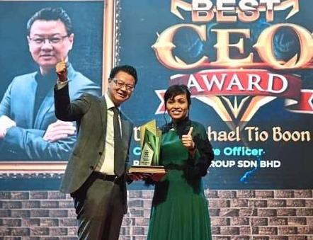 Tio (left) with Deputy Education Minister Teo Nie Ching after being presented with the u201cBest CEOu201d award.