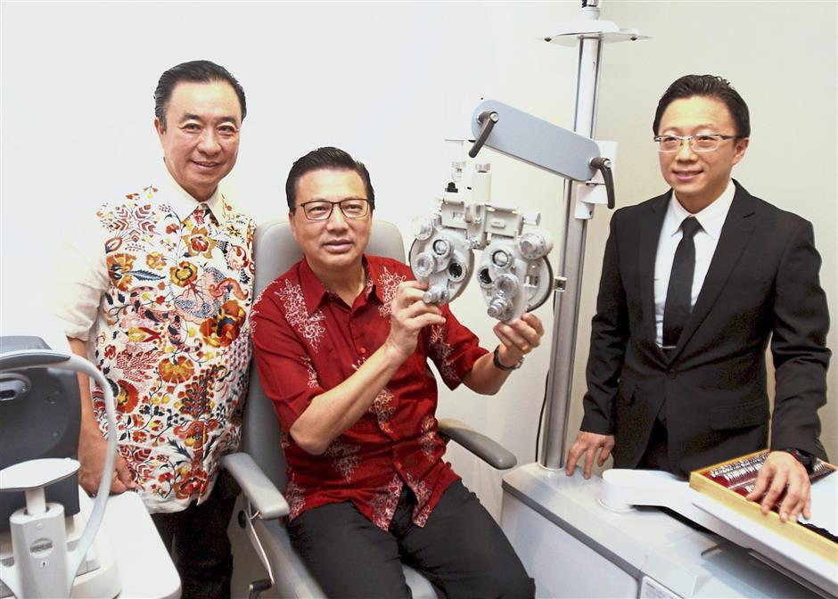 Expansion mode: Liow (centre) getting his eyes checked during the launch. With him are Tan (left) and consultant ophthalmologist Dr Chang Khai Meng.