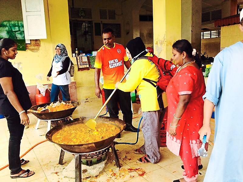 Heartwarming meals: Volunteers cooking a curry dish for flood victims in Kota Baru, Kelantan.