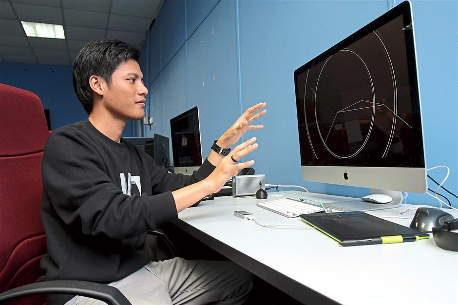 Muhd Syahman using his computer to create art at the Center of Interactive Media , Faculty of Creative Multimedia, Multimedia University.