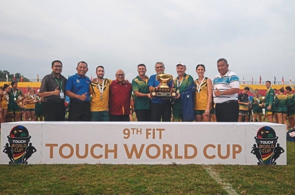 Khalid (fourth from right) holding the FIT Touch World Cup trophy at the closing ceremony.