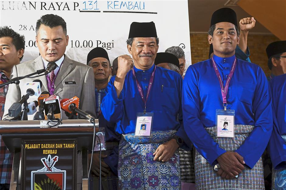 Triumphant: Mohamad Hasan (centre) smiling after he won the Rantau seat unopposed. Looking on is Khairy (right). u2014 Bernama
