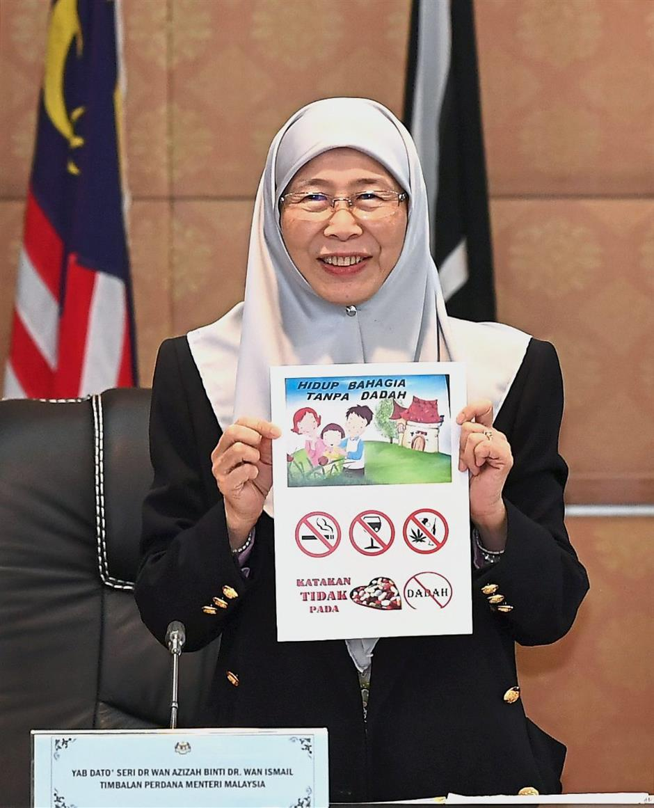A healthy message: Dr Wan Azizah showing the anti-drugs campaign pamphlet to the media after the meeting in Putrajaya. — Bernama