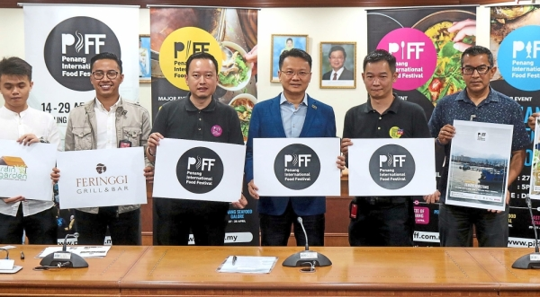 Yeoh (in blue jacket) holding the logo for  the Penang International Food Festival  in Komtar, George Town. Also present are   Ooi (second from left) and Wong (second from right).