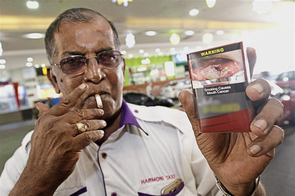 Mohd Kamaruddin showing the health warning on a cigarette packet. He is eager to quit smoking but says it's a slow process.
