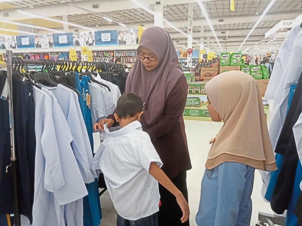 Nor Baidiah helping her son Mohd Iman (left) try on a white shirt.