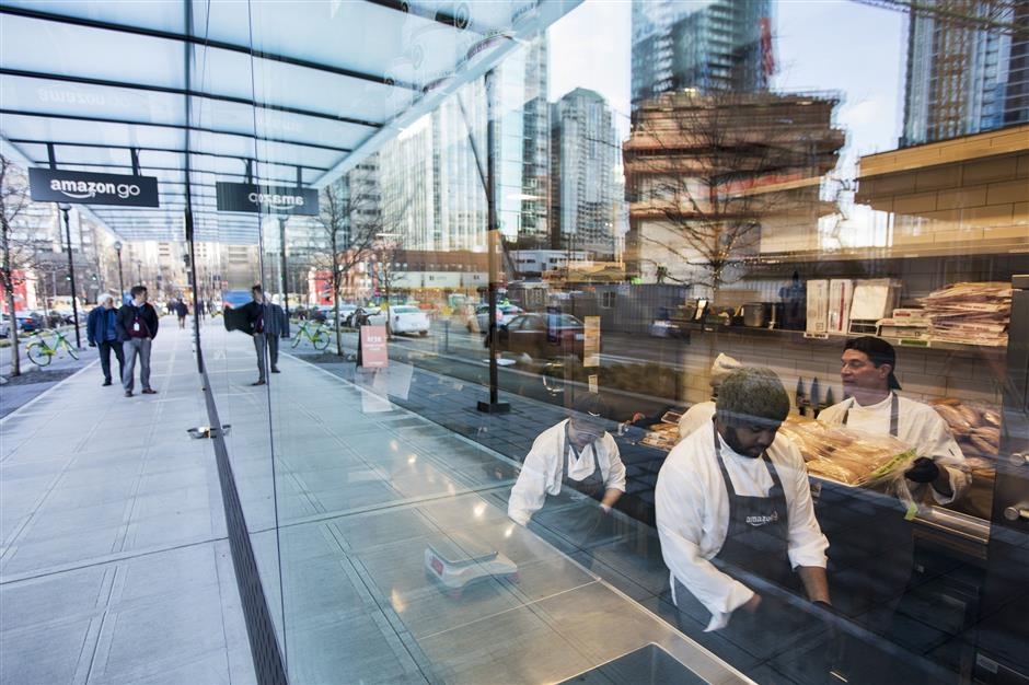 Employees prepare food in the kitchen with a streetside view last week at the Amazon Go store. (Bettina Hansen/The Seattle Times/TNS) OUTS: SEATTLE OUT, USA TODAY OUT, MAGAZINES OUT, TELEVISION OUT, SALES OUT.