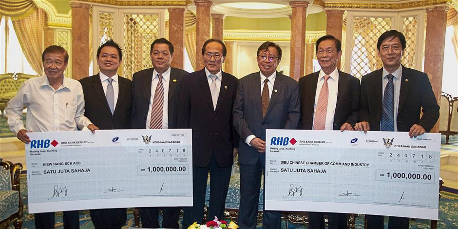 Abang Johari (third right) handing over mock cheques to Hii (centre) and SJK(C) Kiew Nang chairman Tiong Hock Kieng (left) at the Sarawak Legislative Assembly complex in Kuching.