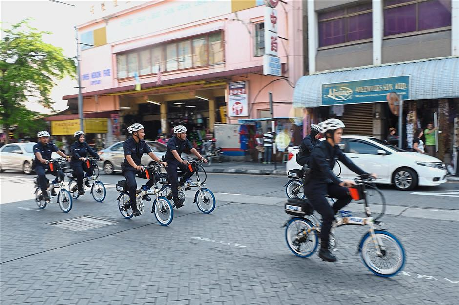 Police personnel patrolling on e-bicycles in George Town, Penang.
