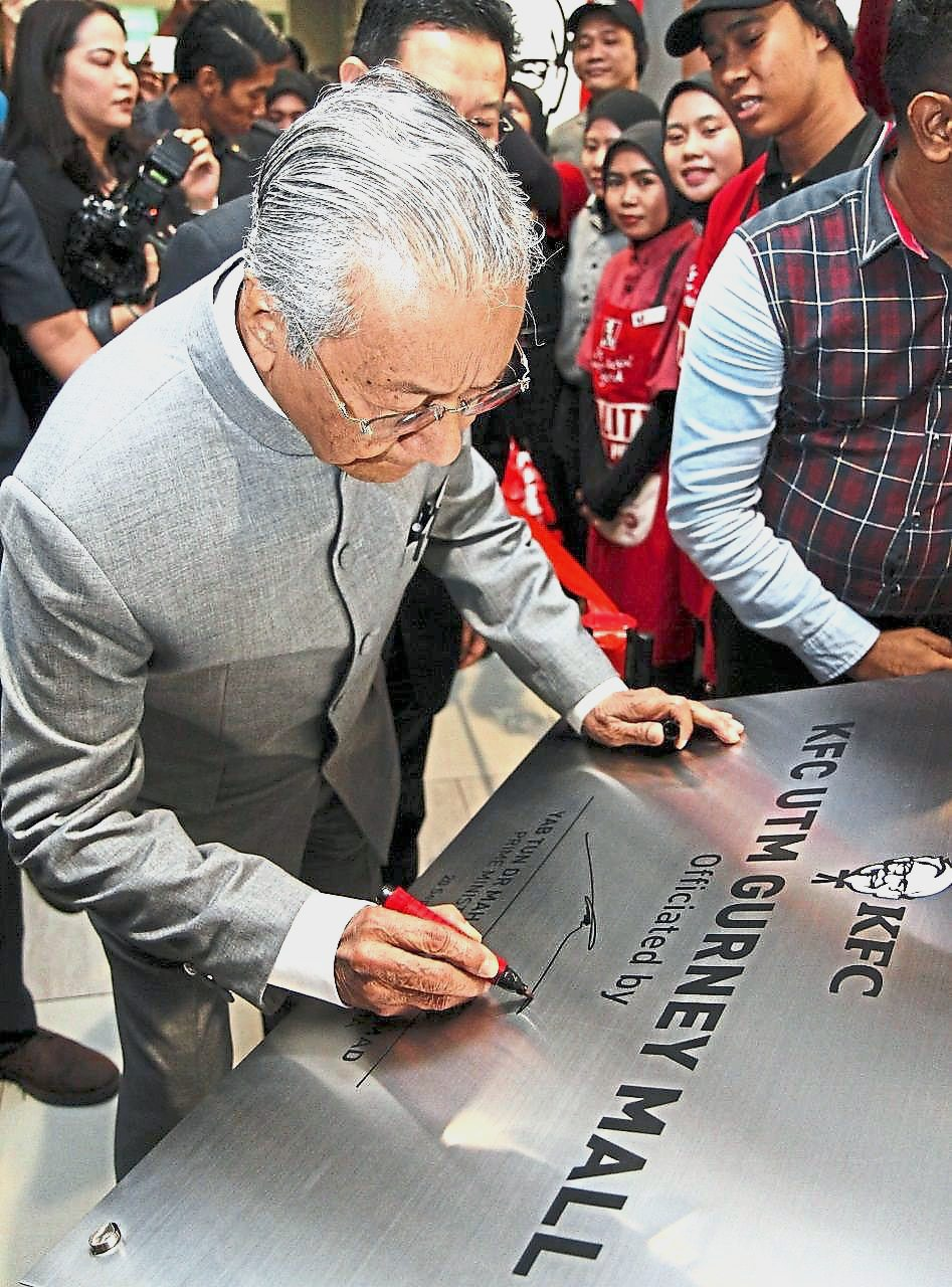Dr Mahathir signing the plaque to officiate at the opening of the KFC outlet in UTM Gurney Mall, Penang.