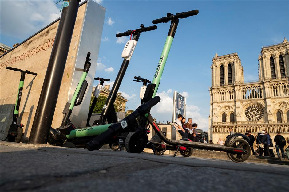 Electric scooters of providers Tier and Bird are pictured on April 1, 2019 in front of Notre-Dame de Paris Cathedral in Paris. - The market for personal mobility devices (EDP for 'engins de deplacement personnel' in French), like electric scooters, electric unicycles and hoverboards, rose by 32 per cent in value in 2018, and was driven by a strong growth of 76 per cent of the electric scooter market, according to a study published April 1, 2019. (Photo by KENZO TRIBOUILLARD / AFP)