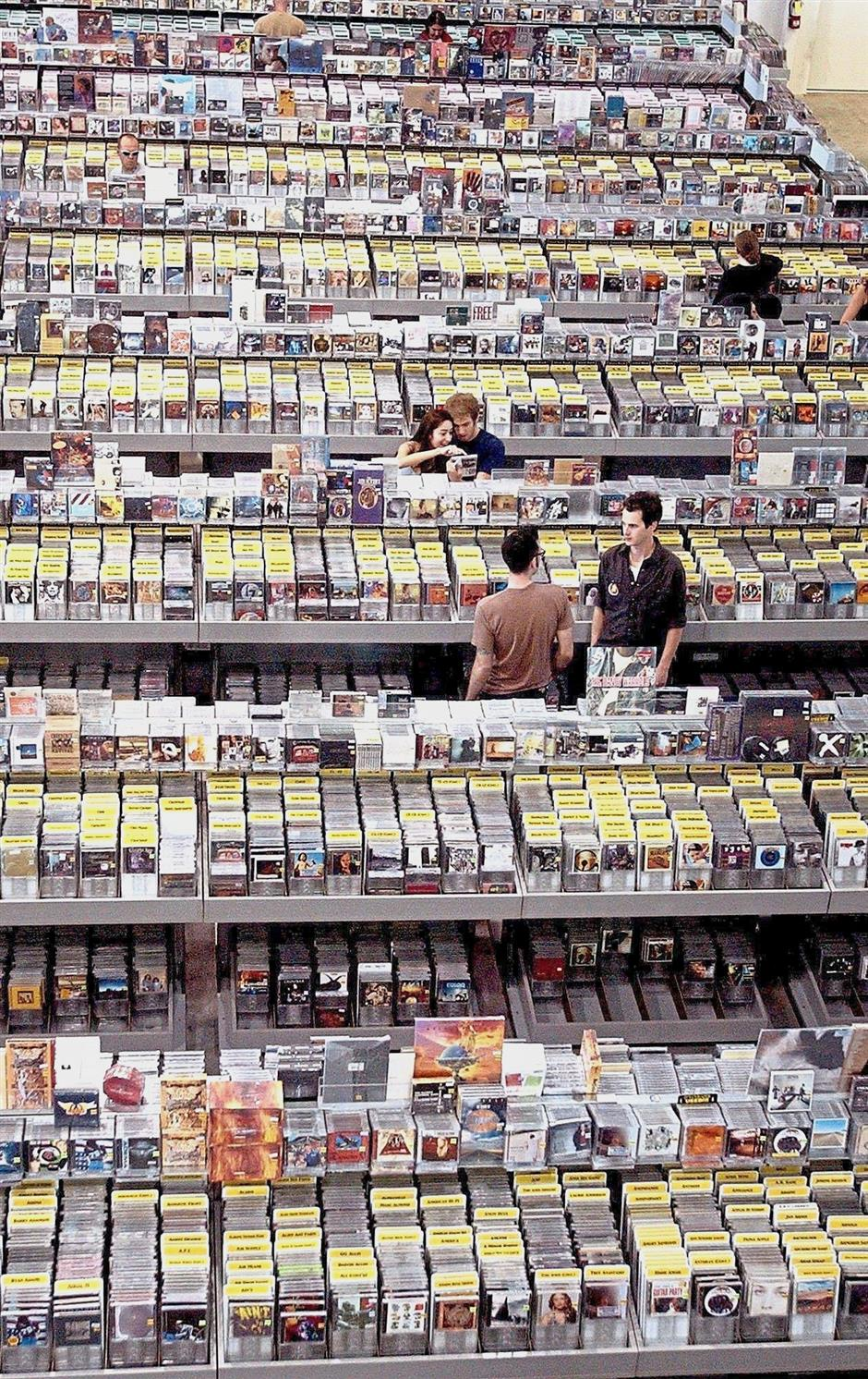 Customers browsing through thousands of titles at a large music store in Los Angeles in the early 2000s. CDs in the US are said to cost between US10 and US15. — AP Photo
