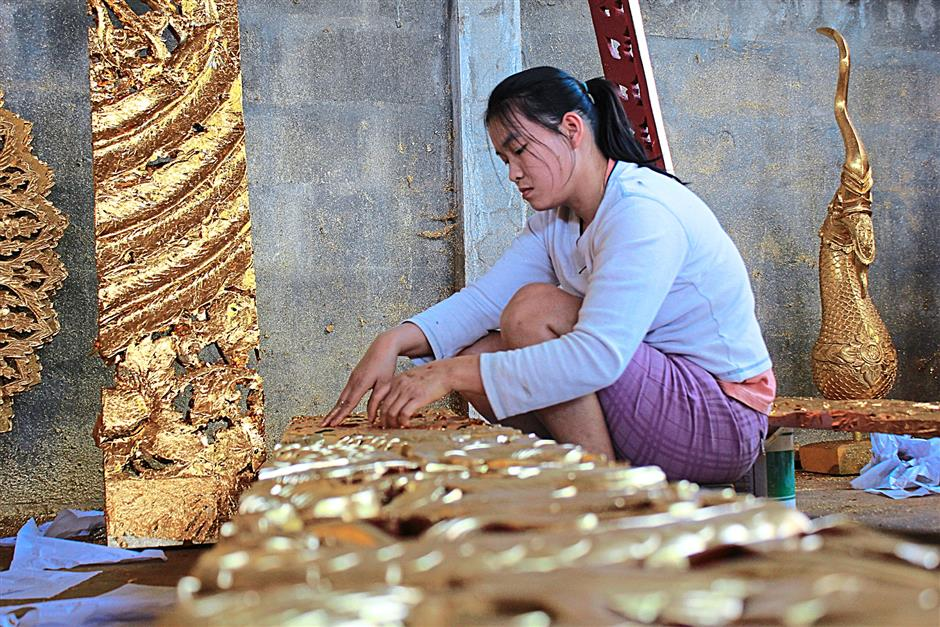 A Baan Tawai craftsman applying layer upon layer of gold foil on her  masterpiece.