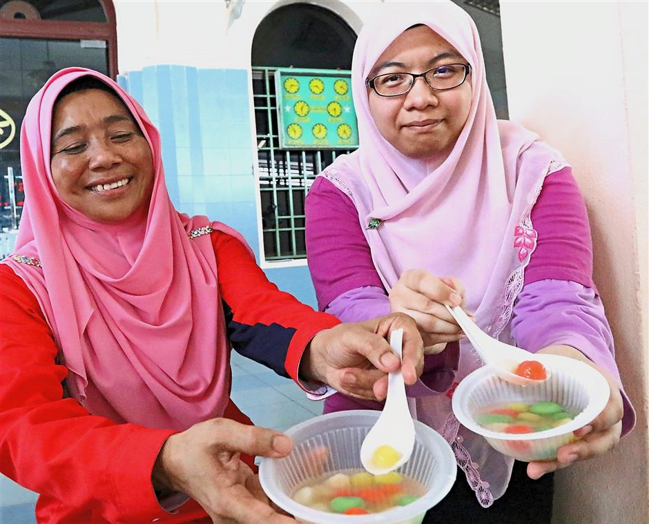 (Above) Farah Nabilah Muhammad Faiz Ghan (in pink) and her mother Che Zainab Awang showing the colourful tang yuan they are about to enjoy. (Right pic) Children trying their hand at rolling the rice balls.