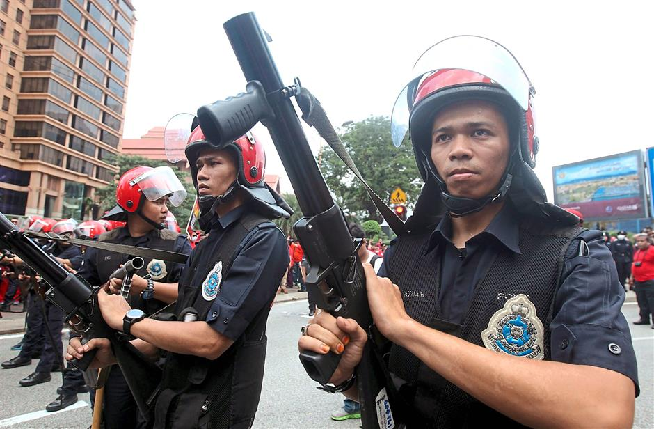 Beefing up security: Policemen are seen standing guard near Pavillion mall.