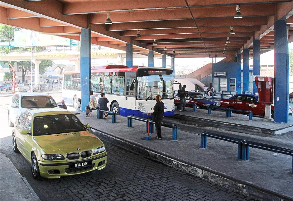 Cars being parked illegally inside the bus terminal as there is insufficient parking space at the commercial area across the street.