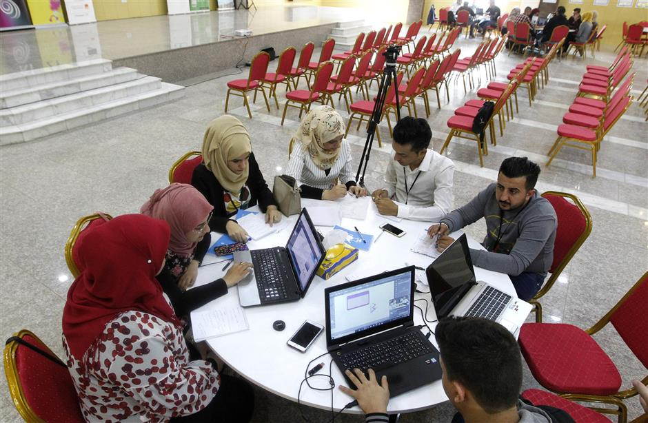 Iraqi youths work at 'The Station', Baghdad's incubator for would-be entrepreneurs, in the Iraqi capital on November 17, 2018. - Stuck between an endless waitlist for a government job and a frail private sector, Iraqi entrepreneurs are taking on staggering unemployment by establishing their own start-ups. The first murmurs of this creative spirit were felt in 2013, but the Islamic State group's sweep across a third of the country the following year put many projects on hold. Now, with IS defeated, co-working spaces and incubators are flourishing in a country whose unemployment rate hovers around 10 percent but whose public sector is too bloated to hire. (Photo by SABAH ARAR / AFP)