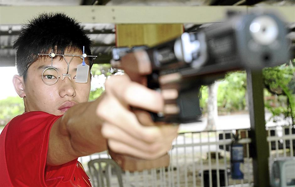 Fine shot: Tong Tat taking aim with his air pistol in training.