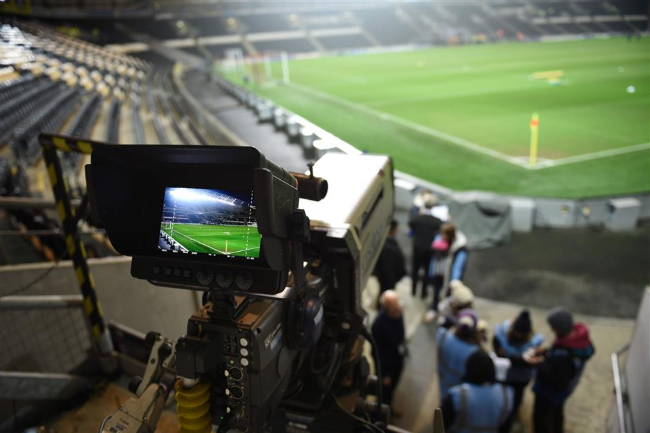 (FILES) This file photo taken on February 10, 2015 shows a television camera is positioned to film the English Premier League football match between Hull City and Aston Villa at the KC Stadium in Hull, north-east England on February 10, 2015. The bulging wallets of Amazon and Facebook could drive up the cost of TV rights for the next English Premier League deal as sport braces for a global broadcasting revolution. Sky and BT shelled out more than u00a35 billion ($6.7 billion) for the privilege of keeping the jewel in the crown of British sports broadcasting for three seasons from 2016-17 but the new kids on the block are flexing their muscles.  / AFP PHOTO / Oli SCARFF / RESTRICTED TO EDITORIAL USE. No use with unauthorized audio, video, data, fixture lists, club/league logos or \'live\' services. Online in-match use limited to 75 images, no video emulation. No use in betting, games or single club/league/player publications.  / TO GO WITH AFP STORY BY PIRATE IRWIN