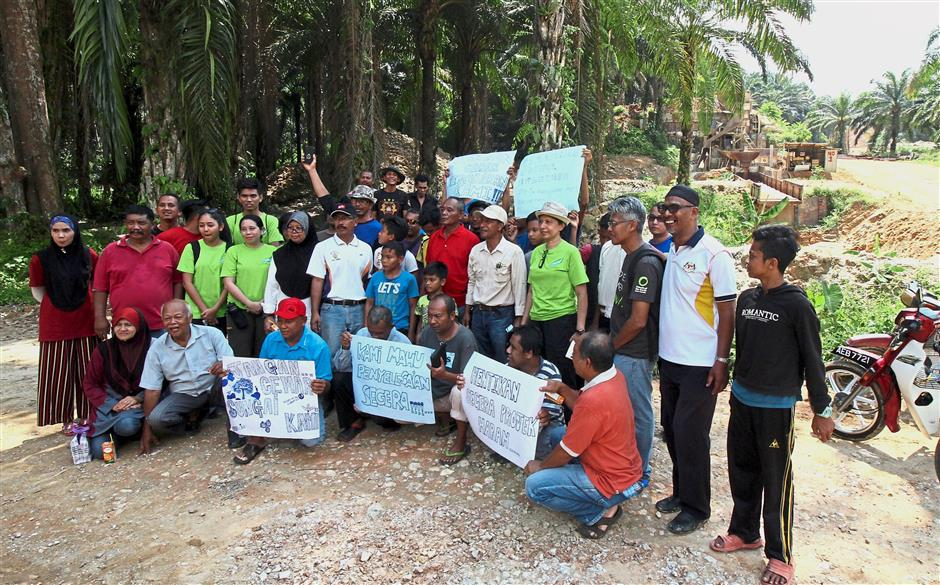 Villagers holding up banners to protest against the mining activity.
